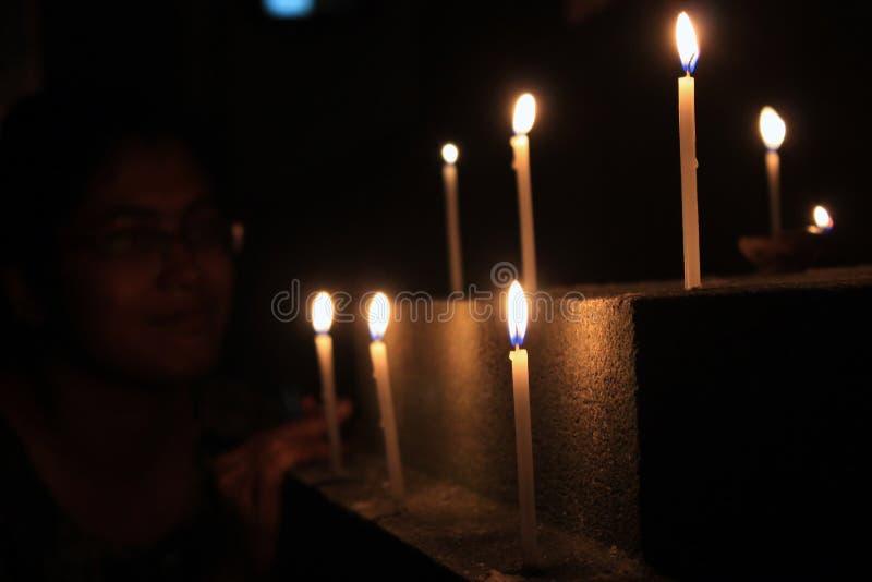 Τα κεριά φλογών θεωρούν την έννοια Κεριά σε μια σειρά Προσευχή γυναικών στοκ εικόνες