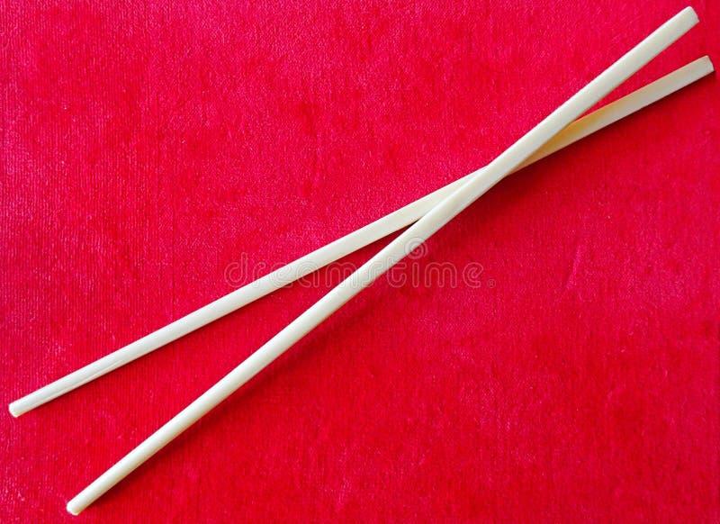 Τα κινέζικα κολλούν Chopsticks για τα ασιατικά τρόφιμα τρώγοντας στο κόκκινο υπόβαθρο στοκ εικόνες