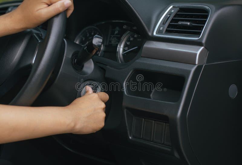 Τα κλειδιά αυτοκινήτων εκμετάλλευσης οδηγών γυναικών χεριών και αρχίζουν τη μηχανή με το σύγχρονο αυτοκίνητο στοκ εικόνα με δικαίωμα ελεύθερης χρήσης