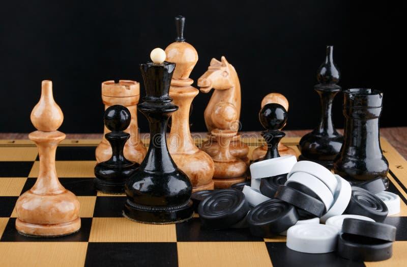 Τα κομμάτια σκακιού και ο σωρός των ελεγκτών που τοποθετούνται στη σκακιέρα στοκ φωτογραφία με δικαίωμα ελεύθερης χρήσης