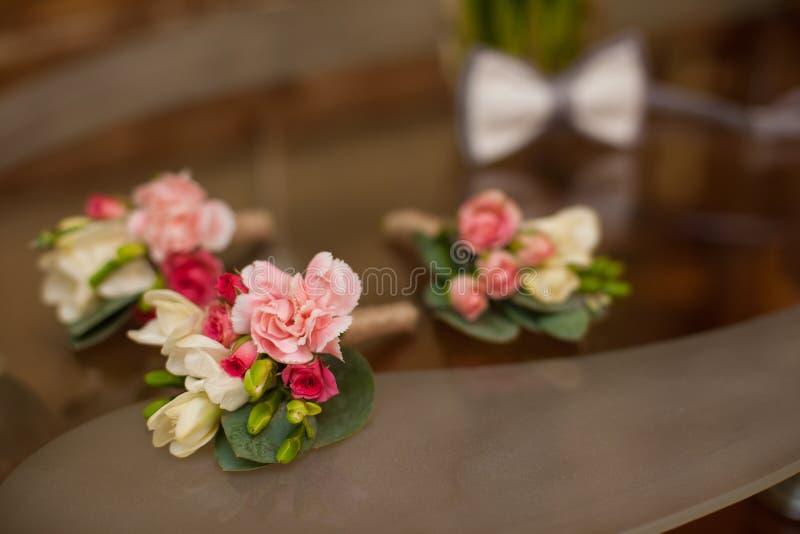 Τα κομψά φρέσκα λουλούδια αυξήθηκαν μπουτονιέρα στην επιτραπέζια κινηματογράφηση σε πρώτο πλάνο στοκ εικόνα