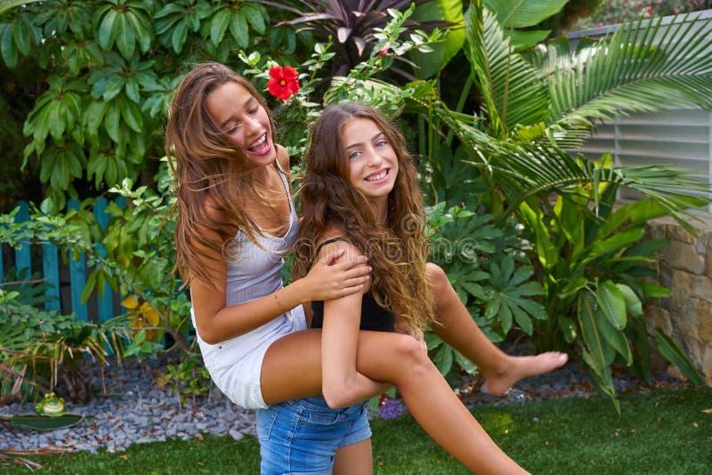Τα κορίτσια εφήβων καλύτερων φίλων piggyback στο κατώφλι στοκ φωτογραφίες