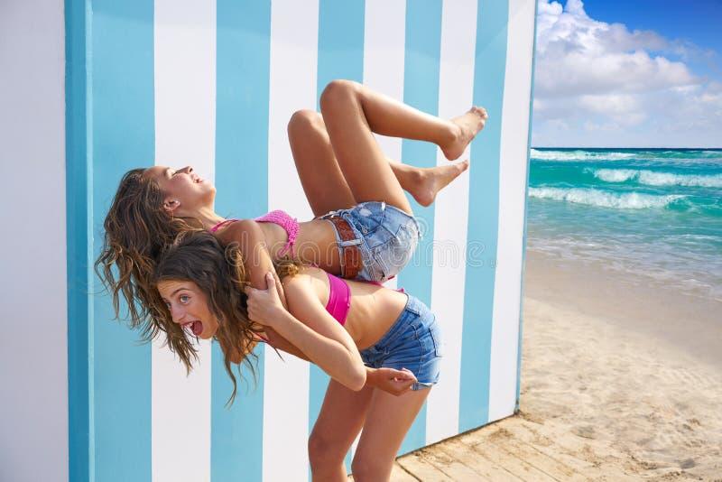 Τα κορίτσια καλύτερων φίλων piggyback στη θερινή παραλία στοκ εικόνα