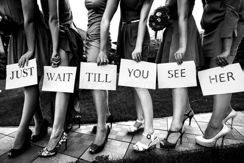 Τα κορίτσια κρατούν ότι μια εγγραφή «περιμένει ακριβώς μέχρης ότου την βλέπετε» από προ τους στοκ εικόνες