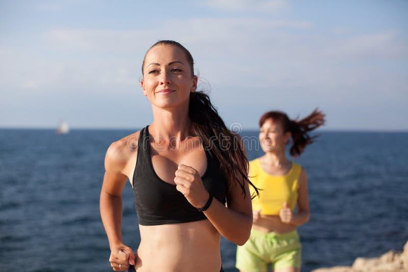 Τα κορίτσια παίζουν τον αθλητισμό που τρέχει γύρω στην παραλία στοκ φωτογραφίες