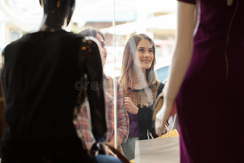 Τα κορίτσια που εξετάζουν έναν ιματισμό αποθηκεύουν την επίδειξη στοκ φωτογραφία