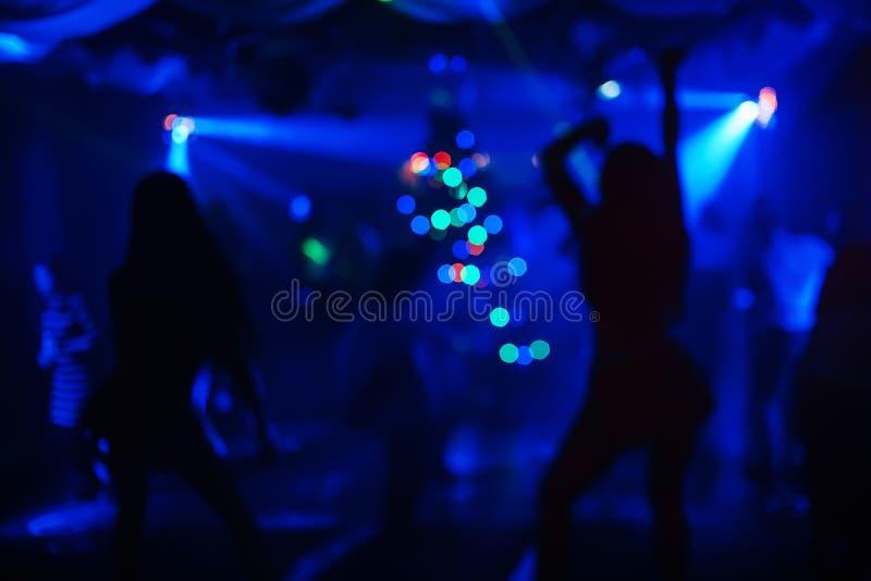 Τα κορίτσια χορεύουν στη λέσχη νύχτας στη σκηνή μερικές θολωμένες σκιαγραφίες στοκ εικόνες