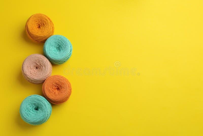 Τα κουβάρια του πλεξίματος των νημάτων στο υπόβαθρο χρώματος, επίπεδο βάζουν με το διάστημα για το κείμενο στοκ φωτογραφίες