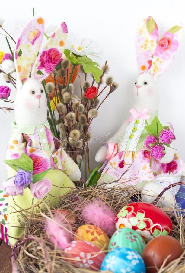 Τα κουνέλια εξετάζουν το καλάθι με τα ζωηρόχρωμα αυγά για Πάσχα στοκ εικόνες