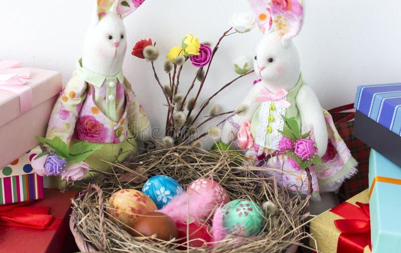 Τα κουνέλια εξετάζουν το καλάθι με τα ζωηρόχρωμα αυγά για Πάσχα στοκ εικόνα με δικαίωμα ελεύθερης χρήσης