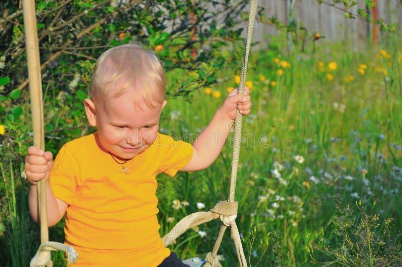 Τα κουνήματα μικρών παιδιών σε μια ταλάντευση στοκ φωτογραφίες
