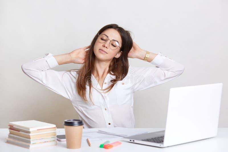 Τα κουρασμένα θηλυκά τεντώματα στο χώρο εργασίας, φορούν το άσπρο πουκάμισο και τα θεάματα, αισθάνονται καταπονημένα, κάθονται μπ στοκ φωτογραφίες