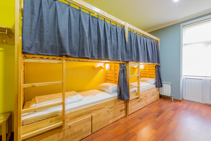 Τα κρεβάτια κοιτώνων ξενώνων τακτοποίησαν στο δωμάτιο στοκ φωτογραφίες