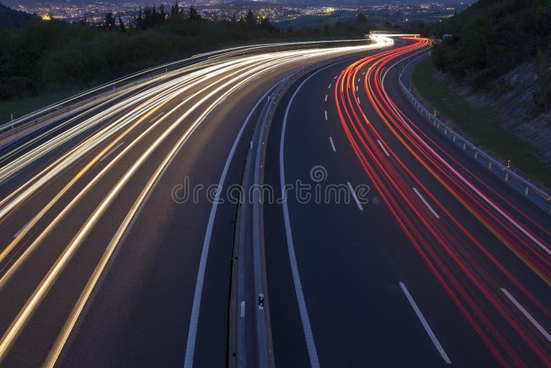 Τα κόκκινα και άσπρα φω'τα, αυτοκίνητα πηγαίνουν στην πόλη στοκ φωτογραφίες