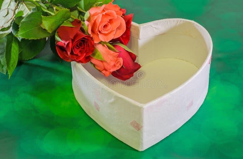 Τα κόκκινα και πορτοκαλιά λουλούδια τριαντάφυλλων με το κιβώτιο μορφής καρδιών, ημέρα βαλεντίνων, υπόβαθρο πράσινου φωτός bokeh,  στοκ εικόνα