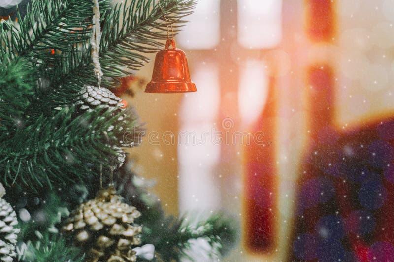 Τα κόκκινα κουδούνια κρεμούν στα χριστουγεννιάτικα δέντρα και το διακοσμητικό εξοπλισμό snowflake που πέφτει με ακτινοβολεί, με τ στοκ φωτογραφία με δικαίωμα ελεύθερης χρήσης