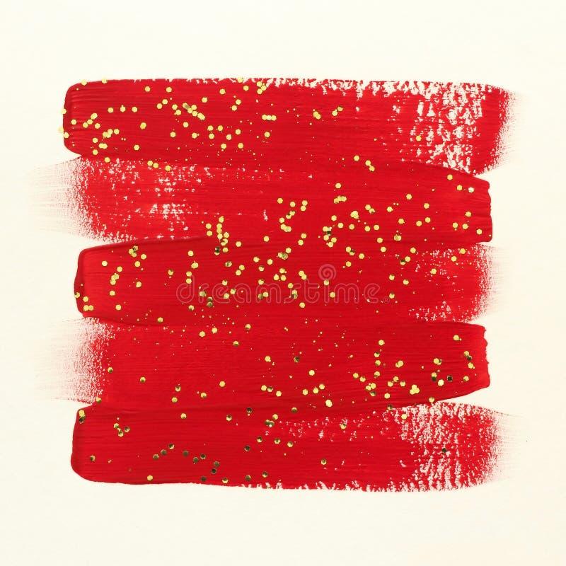 Τα κόκκινα κτυπήματα βουρτσών χρωμάτων με το χρυσό ακτινοβολούν στοκ φωτογραφία