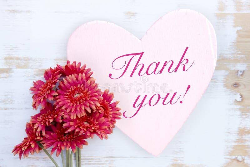 Τα κόκκινα λουλούδια και η ξύλινη καρδιά με τις λέξεις σας ευχαριστούν στοκ εικόνα με δικαίωμα ελεύθερης χρήσης