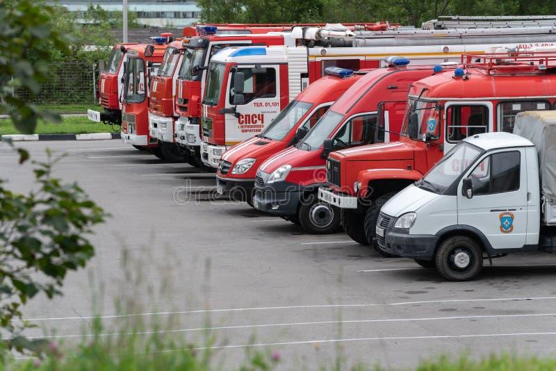 Τα κόκκινα πυροσβεστικά οχήματα πυροσβεστικών αντλιών EMERCOM της Ρωσίας στέκονται επί του τόπου της εξειδικευμένης μονάδας πυρκα στοκ εικόνα
