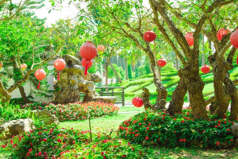 Τα κόκκινα φανάρια που κρεμούν στον κήπο με τα δέντρα και την πράσινη χλόη στοκ φωτογραφία με δικαίωμα ελεύθερης χρήσης