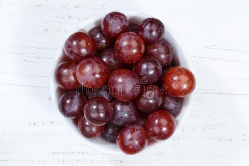 Τα κόκκινα φρούτα φρούτων σταφυλιών κυλούν άνωθεν τον ξύλινο πίνακα στοκ εικόνα με δικαίωμα ελεύθερης χρήσης