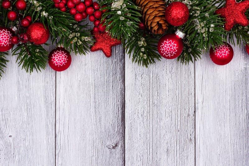 Τα κόκκινα Χριστούγεννα διακοσμούν και τοπ σύνορα κλάδων στο άσπρο ξύλο στοκ φωτογραφία