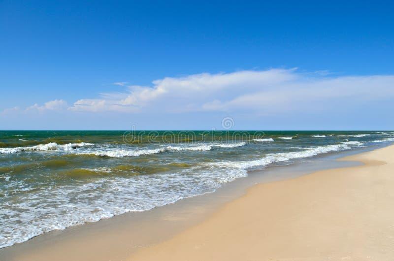 Τα κύματα θάλασσας πλένουν την παραλία ενάντια σε έναν μπλε ουρανό Τοπίο σε μια άγρια παραλία στοκ φωτογραφίες με δικαίωμα ελεύθερης χρήσης