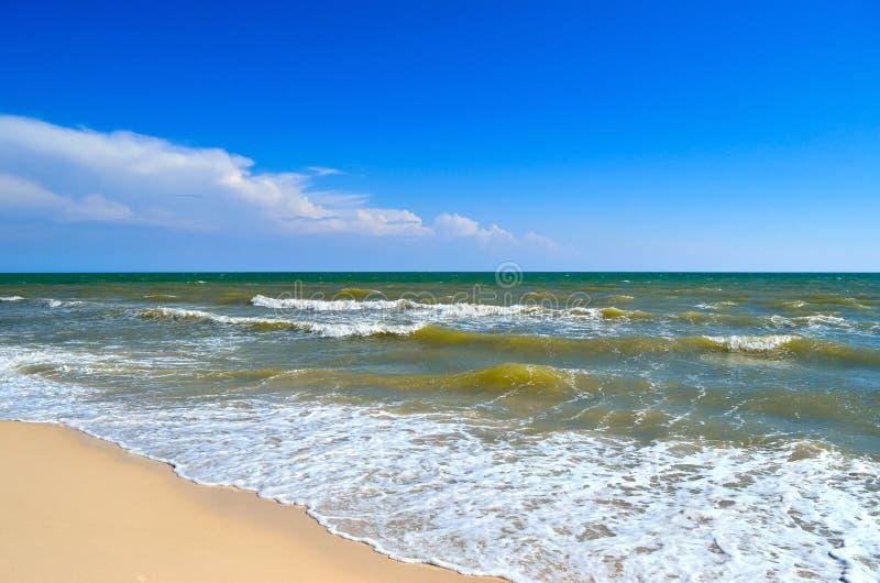 Τα κύματα θάλασσας πλένουν την παραλία ενάντια σε έναν μπλε ουρανό Τοπίο σε μια άγρια παραλία στοκ εικόνες