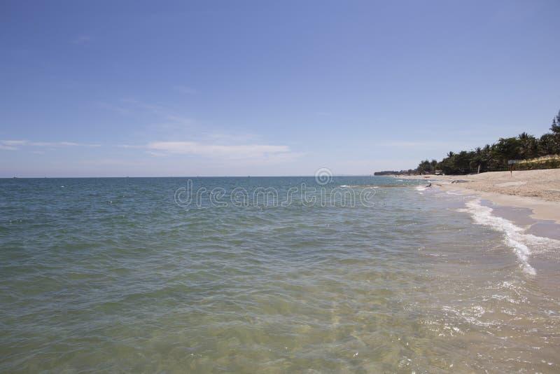 Τα κύματα θάλασσας χτυπούν τη mossy δύσκολη παραλία με τα όμορφα μπλε σύννεφα και την άσπρη άμμο στοκ εικόνα