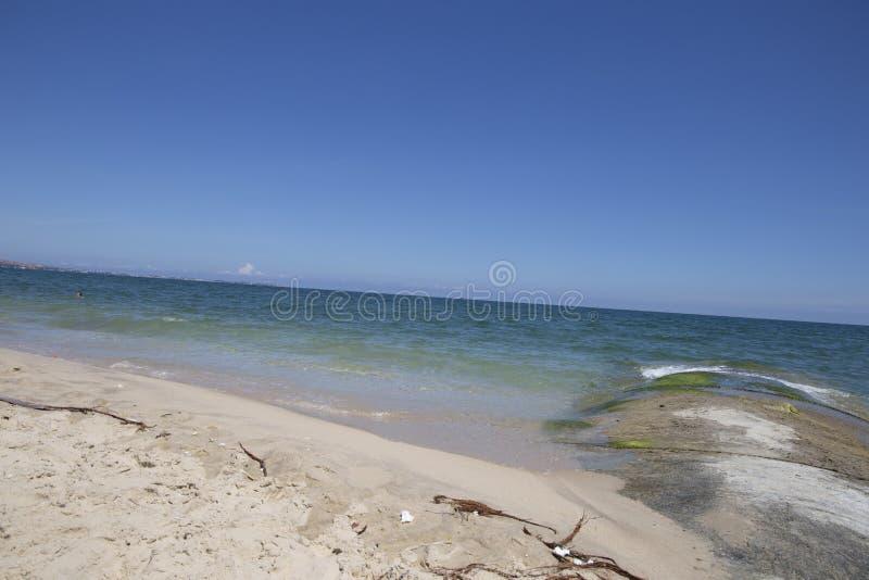 Τα κύματα θάλασσας χτυπούν τη mossy δύσκολη παραλία με τα όμορφα μπλε σύννεφα και την άσπρη άμμο στοκ φωτογραφία με δικαίωμα ελεύθερης χρήσης
