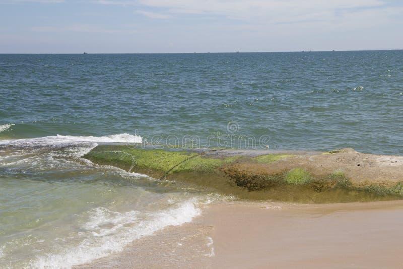 Τα κύματα θάλασσας χτυπούν τη mossy δύσκολη παραλία με τα όμορφα μπλε σύννεφα και την άσπρη άμμο στοκ εικόνες με δικαίωμα ελεύθερης χρήσης