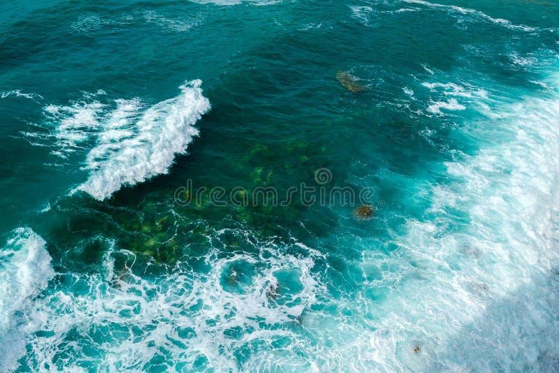 Τα κύματα θάλασσας χωρίζουν στις πέτρες της ακτής την οργιμένος θάλασσα και τον αφρό επάνω από την όψη Πράσινη ανασκόπηση στοκ φωτογραφία