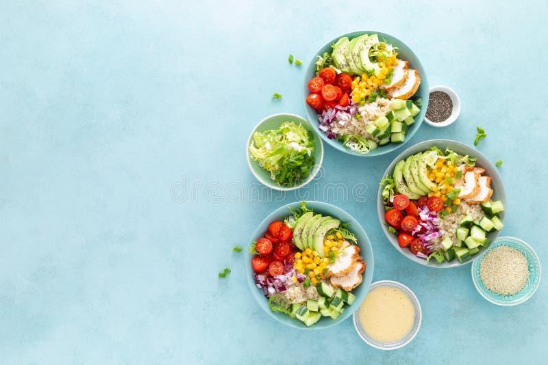 Τα κύπελλα μεσημεριανού γεύματος με ψημένος στη σχάρα το κρέας, το ρύζι και η φρέσκια σαλάτα του αβοκάντο, των αγγουριών, του καλ στοκ φωτογραφία