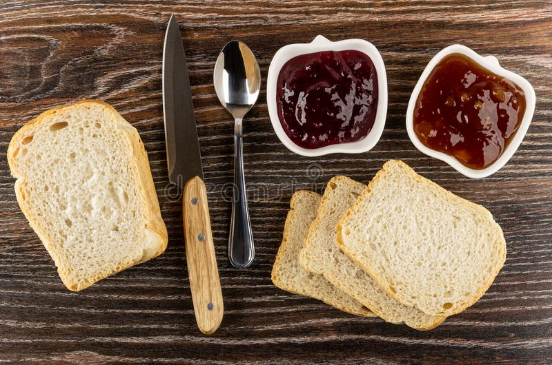 Τα κύπελλα με το βερίκοκο φράσσουν, μαρμελάδα σταφίδων, κουτάλι, μαχαίρι, φέτες του ψωμιού στον ξύλινο πίνακα r στοκ εικόνα με δικαίωμα ελεύθερης χρήσης