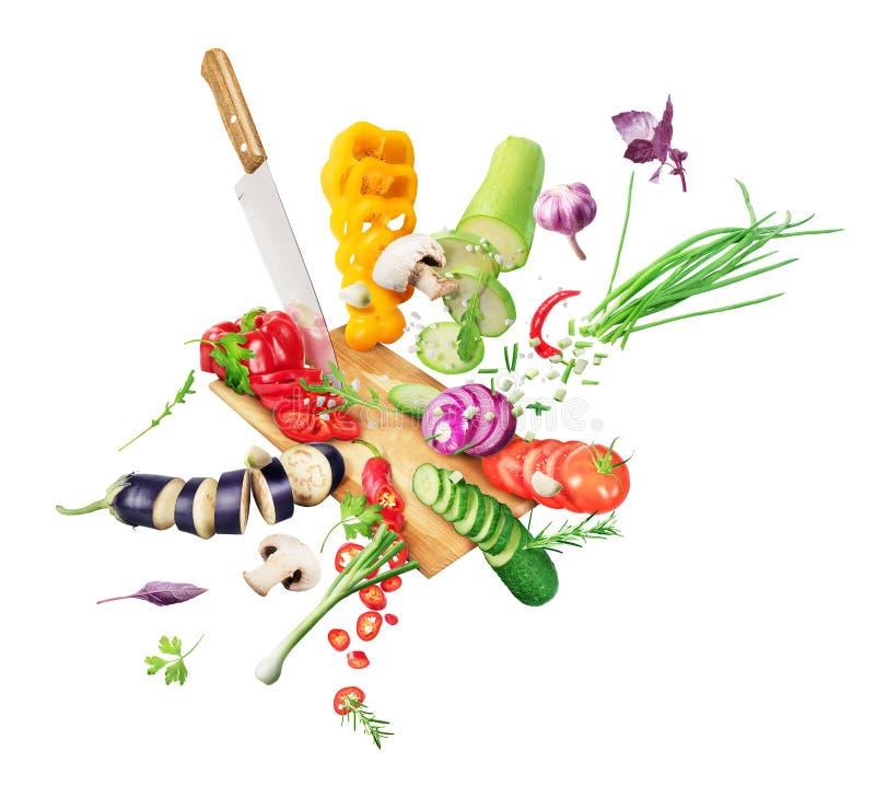 Τα λαχανικά πέφτουν στο τραπέζι και κόβονται με μαχαίρι στοκ εικόνες