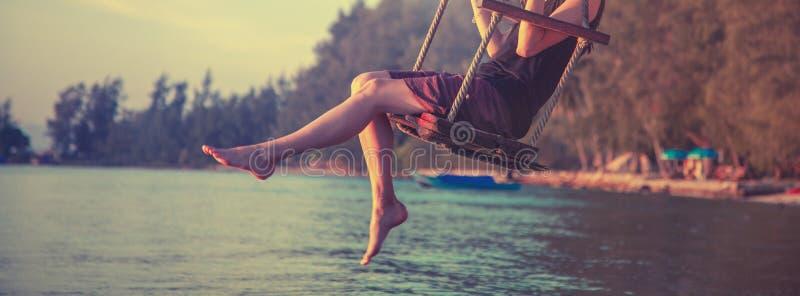 Τα λεπτά θηλυκά πόδια κλείνουν επάνω, ταλάντευση γυναικών σε μια ταλάντευση στην παραλία κατά τη διάρκεια του ηλιοβασιλέματος, υπ στοκ εικόνα