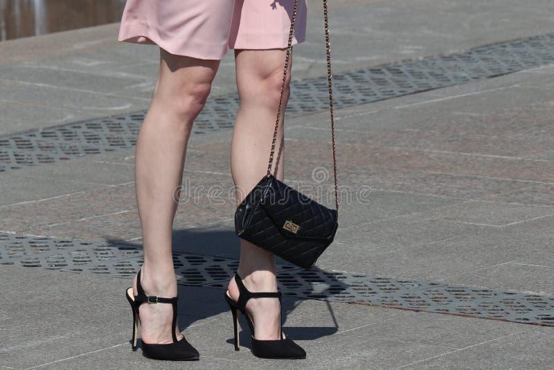 Τα λεπτά θηλυκά πόδια στα υψηλά τακούνια, κομψή γυναίκα στο ρόδινο φόρεμα στέκονται στην οδό με τη μαύρη τσάντα στοκ εικόνα
