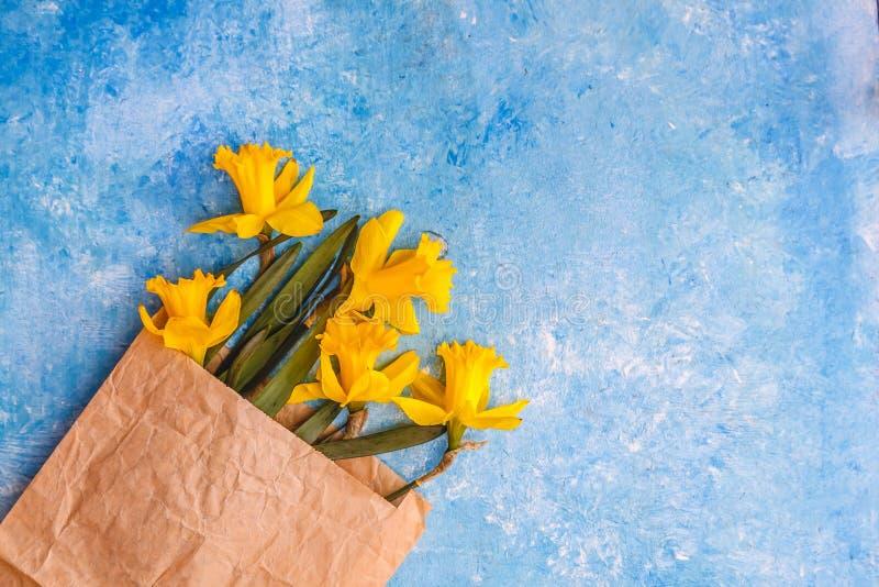 Τα λουλούδια των daffodils είναι κίτρινα σε ένα μπλε μαρμάρινο υπόβαθρο σε μια τσάντα εγγράφου επεξεργασίας, υπάρχει ένα κενό διά στοκ εικόνα