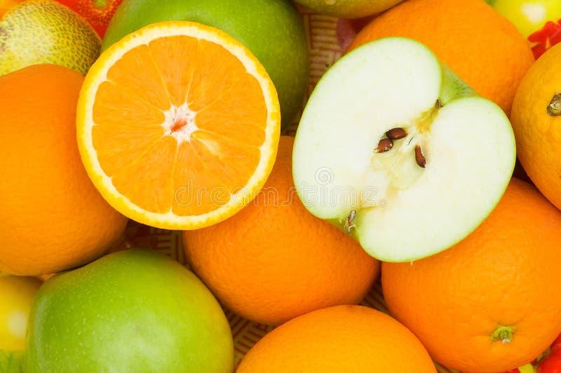 τα μήλα κλείνουν τα μισά πορτοκάλια αποκοπών επάνω στοκ φωτογραφίες