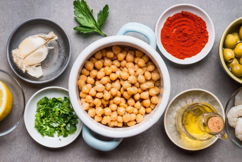 Τα μαγειρεύοντας συστατικά στα κύπελλα για Chickpea τη σαλάτα στο γκρίζο συγκεκριμένο υπόβαθρο, τοπ άποψη, κλείνουν επάνω στοκ εικόνα