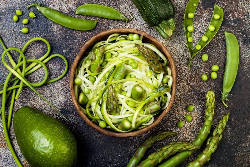 Τα μακαρόνια ή τα νουντλς κολοκυθιών zoodles κυλούν με τα πράσινα veggies και το pesto σκόρδου scape Τοπ άποψη, υπερυψωμένη στοκ εικόνα με δικαίωμα ελεύθερης χρήσης