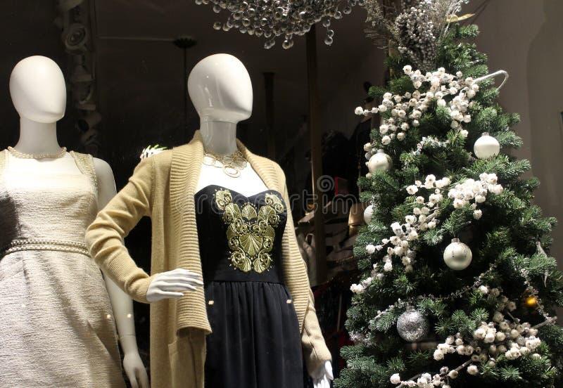 Τα μανεκέν έντυσαν στη μόδα Χριστουγέννων με τις διακοσμήσεις και τα στοιχεία για την πώληση στο παράθυρο storefront, Saratoga Sp στοκ εικόνες