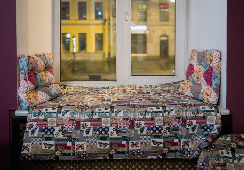 Τα μαξιλάρια και τα στρώματα βρίσκονται στο windowsill ως καναπές για τη χαλάρωση στοκ φωτογραφία με δικαίωμα ελεύθερης χρήσης
