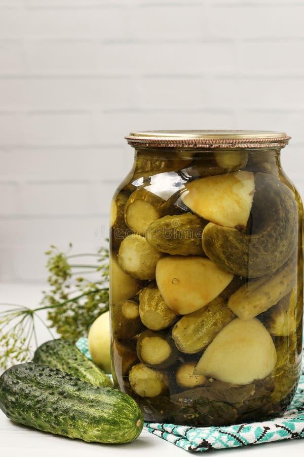 Τα μαριναρισμένα αγγούρια με τα μήλα σε ένα βάζο βρίσκονται σε ένα άσπρο υπόβαθρο στοκ φωτογραφία με δικαίωμα ελεύθερης χρήσης