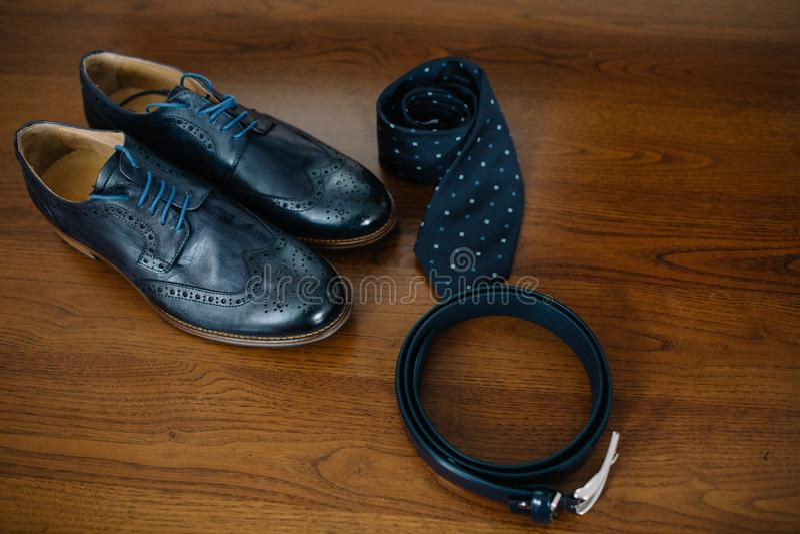 Τα μαύρα παπούτσια δέρματος, το χρυσό ρολόι, ο ξύλινοι δεσμός τόξων και η ζώνη στέκονται στοκ εικόνες