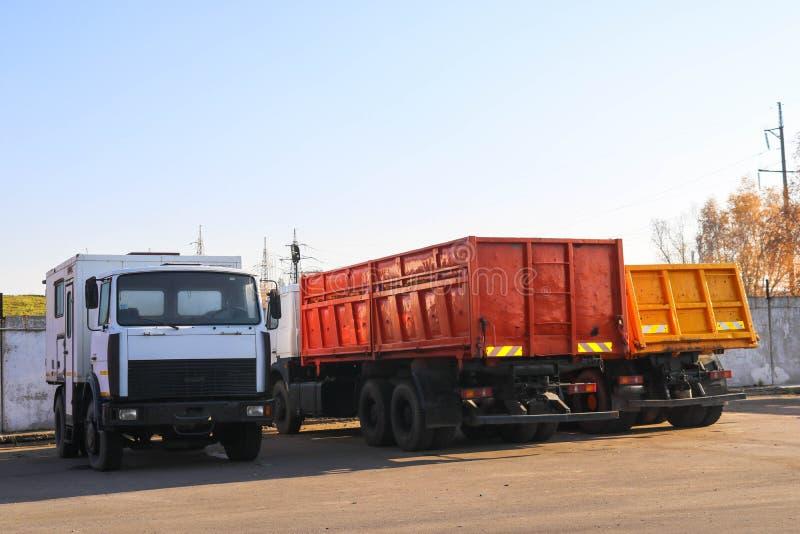 Τα μεγάλα βαριά φορτηγά φορτίου με τα αμάξια και τα ρυμουλκά, φορτηγά απορρίψεων στέκονται σε μια σειρά στο χώρο στάθμευσης έτοιμ στοκ φωτογραφία