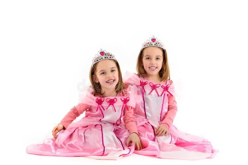 Τα μικρά δίδυμα κορίτσια είναι ντυμένα ως πριγκήπισσα στο ροζ στοκ εικόνες