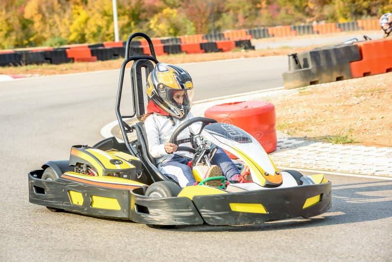Τα μικρά κορίτσια οδηγούν πηγαίνουν αυτοκίνητο Kart σε ένα tra αγώνα παιδικών χαρών στοκ εικόνες