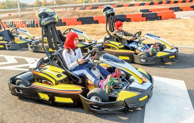 Τα μικρά κορίτσια που προετοιμάζονται να οδηγήσουν πηγαίνουν αυτοκίνητο Kart σε ένα RA παιδικών χαρών στοκ φωτογραφία με δικαίωμα ελεύθερης χρήσης