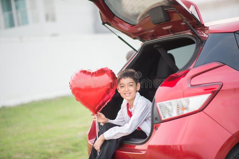 Τα μικρά παιδιά που κάθονται στη πίσω πόρτα του αυτοκινήτου με την καρδιά μπαλονιών δίνουν στοκ εικόνες